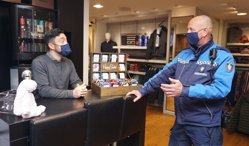 <p>BOA Jeroen Stam in gesprek met Carlos van Wees over de mondkapjesplicht. Wat moet je doen als er iemand binnen komt zonder kapje? Foto: VSK </p>