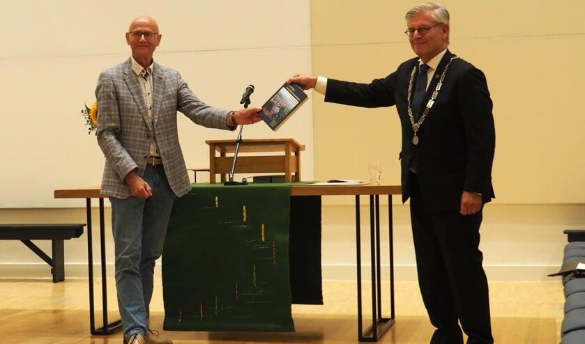 Burgemeester Aptroot krijgt het eerste exemplaar van '1000 jaar Dorpskerk' uitgereikt