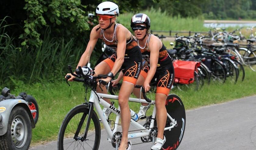 Joleen Hakker achter op de tandem bij begeleidster Linda van Vliet tijdens de Midzomeravondtriathlon.