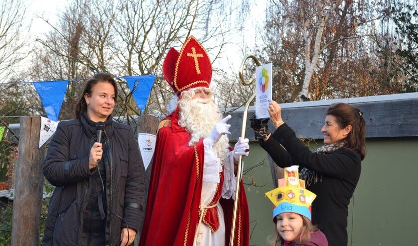 Trots laat directeur Mariella Ditmar het vignet zien aan Sinterklaas (Foto: Inge Koot).