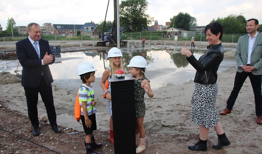 Fien, Fien en Abel hebben de eerste paal helpen slaan. De wethouder, de schooldirecteur en de bouwer zijn blij.