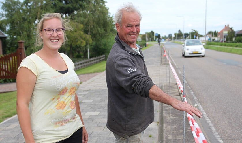Jolanda en Ton de Vreede zijn tegen het plan om tussen het fietspad en de weg een haag te maken. Ze hebben een lint gespannen om aan te geven hoe hoog die haag zou kunnen worden.