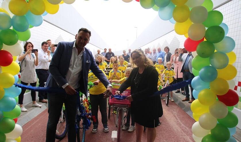 Wethouder Ilona Jense en Huib van der Ven van het gelijknamige aannemersbedrijf knippen een lint door en daarna kunnen de leerlingen van de Johannesschool de tunnel fietsend openen.