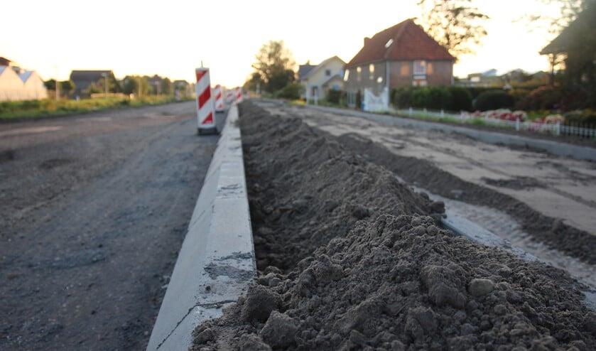 Ook Gemeentebelangen wil weten waarom de weg aan 'de huizenkant'25 centimeter hoger moet worden.