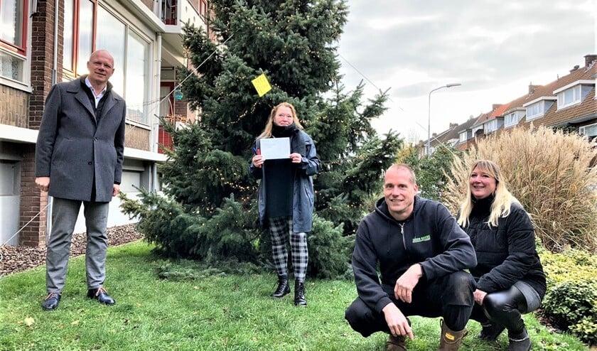 <p>Burgemeester Klaas Tigealaar kwam hoogstpersoonlijk langs op de Von Geusaustraat om de vergunning te overhandigen en zelf ook een kerstwens in de boom te hangen (foto: gemeente LV).</p>