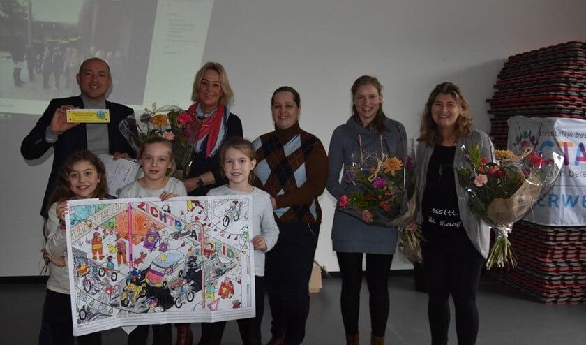 Op de foto directeur Robin van Eekert, managementassistente Annelies Feenstra, wethouder Ilona Jense, Maaike van den Berg en Wendy Holtzapfel. Vooraan leerlingen met tekentalent.
