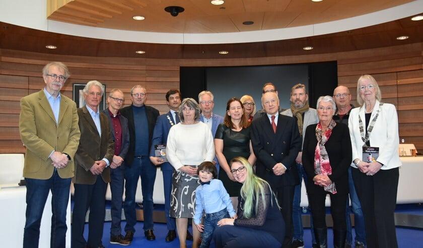 Dertien Oostlandse schrijvers, plus een gastschrijfster, op de foto met burgemeester Van de Stadt van Lansingerland en burgemeester Ravestein.