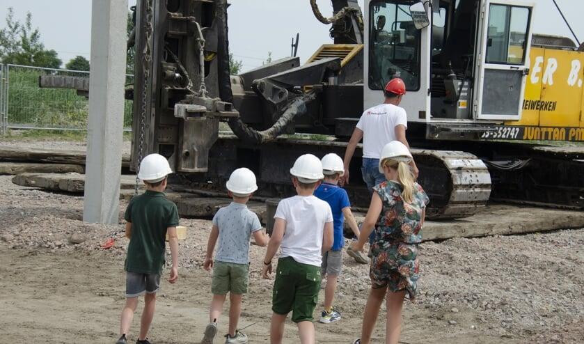 De kinderen van de eigenaren op weg naar hun 'werk': het slaan van de eerste paal.