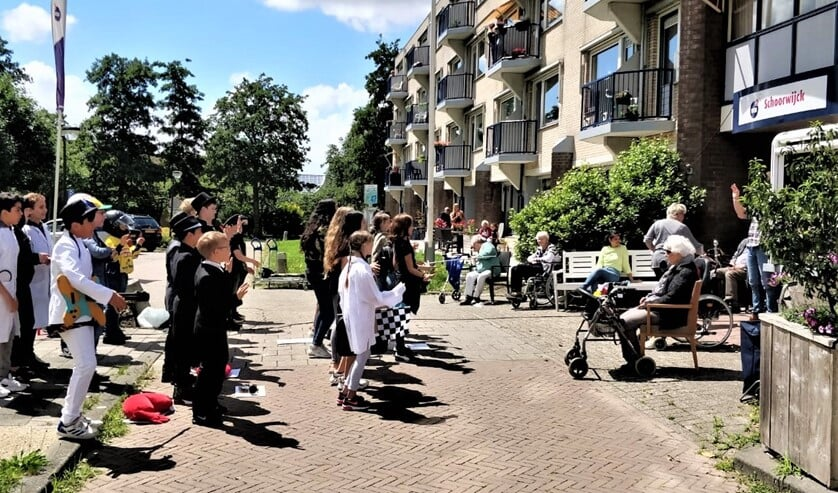 De basisschoolleerlingen voeren hun musical op voor de hoofdingang van WZH Schoorwijck (foto: Ap de Heus).