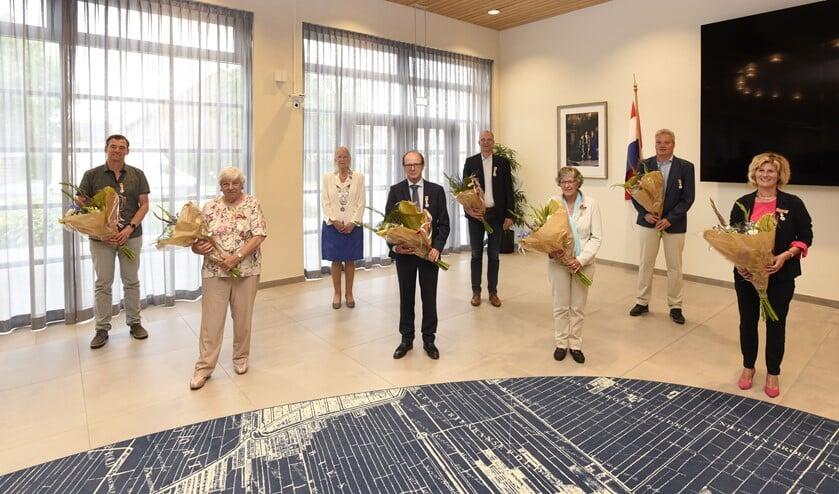 De burgemeester en de zeven gedecoreerden. Van links naar rechts: René Hofman, Wil Bubbert, Joop van den Berg, Hendrik-Jan van der Waal, Joke van Hagen, Jaap Mensink en Connie Slob. (foto Cok van den Berg)