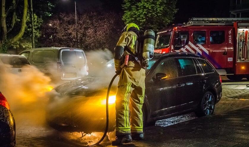 Een brandweerman blust de brandende auto af (foto: Sebastiaan Barel/Regio15).