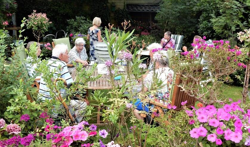 De koffiesoos van wijkcentrum De Boot vond deze keer in een tuin plaats in de schaduw tussen de bloemetjes (foto: pr).