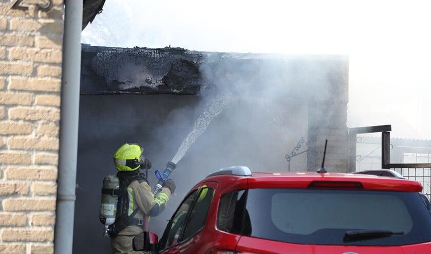 De brandweer blust na bij de brand in een garage naast een woning aan de Wickelaan (foto:Rene Hendriks).