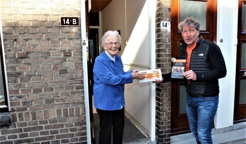 <p>Voorzitter Erik van der Linden overhandigt aan mevr. Zaat, één van de oudste leden van de vereniging, een doos met oranjetompoezen (foto Ap de Heus)</p>