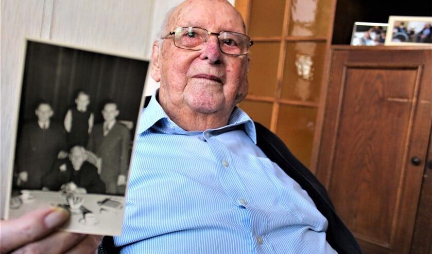 <p>De heer Groenewegen toont een foto met daarop (zittend) zijn grootvader die ook 100 jaar oud werd (foto: Dick Janssen).</p>