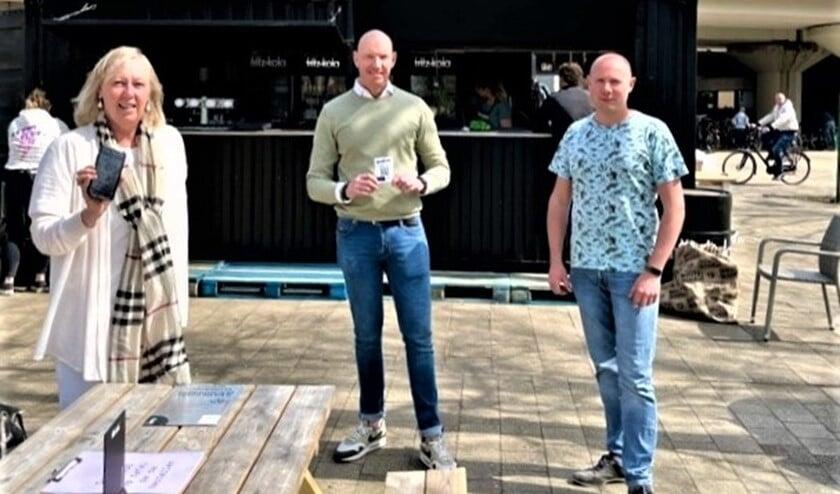 <p>Wethouder Astrid van Eekelen toont app met de horecaondernemers Ricardo Houtman en Eddy Knopjes op Stationsplein (foto: gemeente).</p>