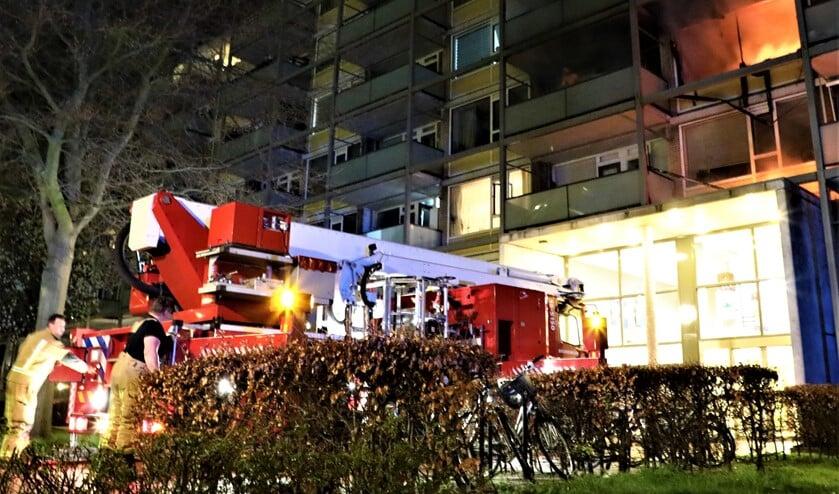 <p>Toen de brandweer aankwam sloegen de vlammen uit het pand en moest de bewoner van het balkon worden gehaald met een hoogwerker (foto: Sebastiaan Barel).</p>