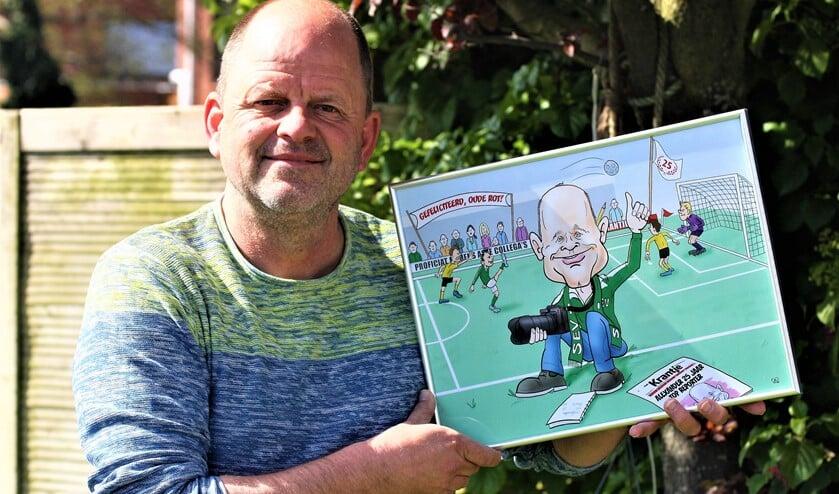 <p>Alexander Wagener met de karikatuurtekening die hij ontving voor zijn 25-jarig jubileum bij Het Krantje (foto: Ben Wagener).</p>
