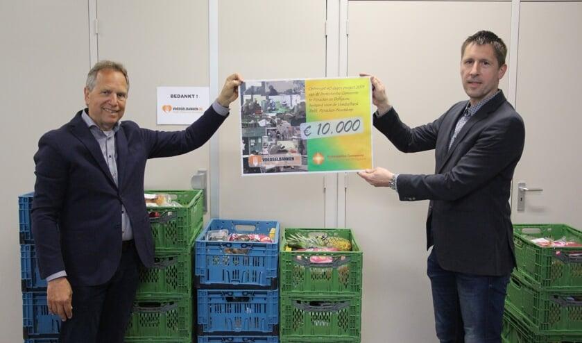 <p>Lennart de Prieëlle (rechts) overhandigt een cheque van 10.000 euro aan voorzitter Peter Vogelaar van de Voedselbank Delft/Pijnacker-Nootdorp.</p>