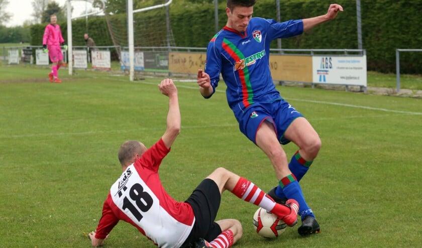 Marcel de Heus (liggend) probeert om de bal niet bij zijn tegenstander in te leveren.