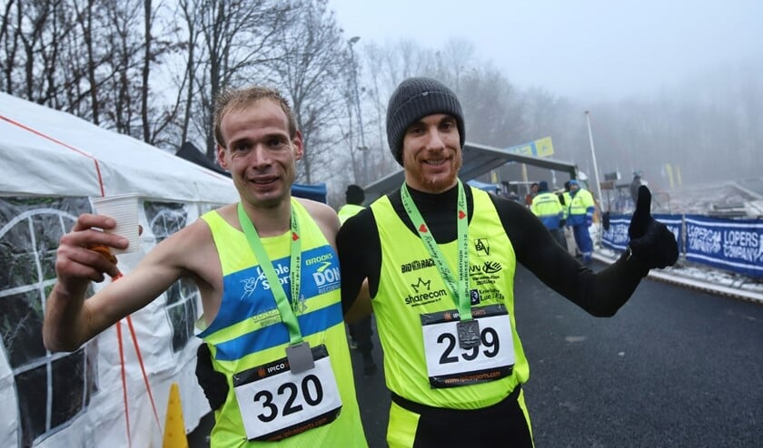 Erwin Harmes (320) met nummer twee Wouter Decock zijn blij na hun finish van de marathon van Spijkenisse. Harmes won in een recordtijd.