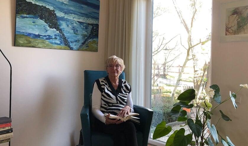 <p>Roos van Houwelingen-Kok voor een van haar zelf gemaakte schilderijen</p>