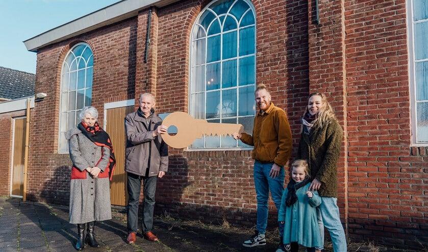 De symbolische sleutel van de Chr. Gereformeerde kerk wordt overhandigd door familie van Bergeijk (links) aan familie de Vries (rechts).