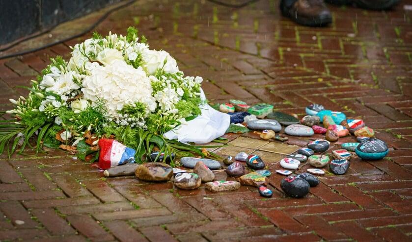 Bij de Stolpersteine liggen naast het bloemstuk van de gemeente een groot aantal zwerfstenen. Het is de bedoeling dat die het verhaal verder gaan verspreiden.