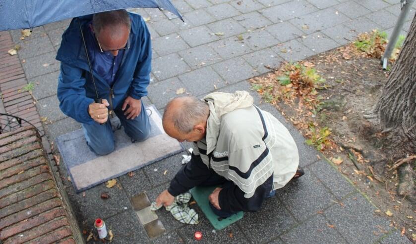 <p>Adrie (r) en Willem Jan nemen de Stolpersteine liefdevol onderhanden. (Tekst & Foto: EvE)</p>