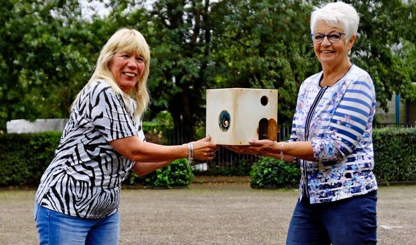 <p>Gerda Melema (r) draagt het kunstwerk over aan Ingrid Verwiel (l) bij de Vierhovenkerk, waar ISOFA - SchuldhulpMaatje Delft spreekuur heeft (Foto: Koos Bommel&eacute;)</p>