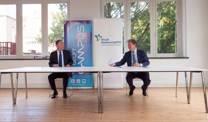 Tim van der Hagen, voorzitter van de TU Delft (links), en Erik Oostwegel, CEO van Royal HaskoningDHV, ondertekenen het Memorandum of Understanding (Foto: TU Delft / Jens Kok)