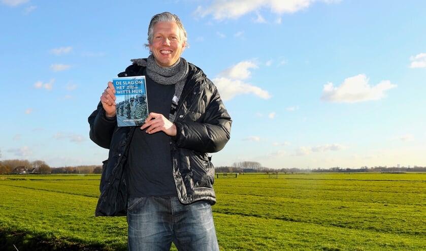 <p>Pieter Uittenbogaard met zijn recent verschenen boek op een van de mooiste plekjes van Delft. Foto: Koos Bommel&eacute;</p>