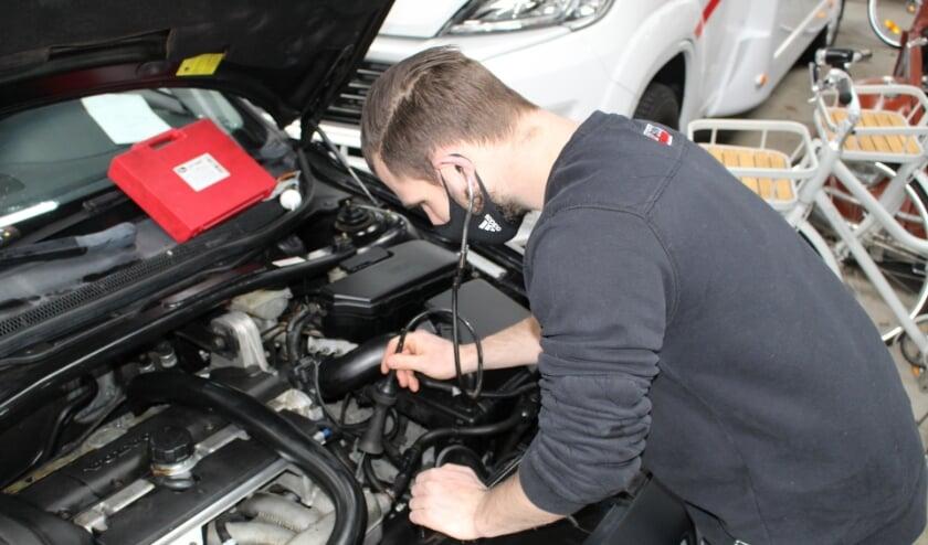 <p>Een monteur luistert met een stethoscoop naar de motor. (Foto: EvE)&nbsp;</p>