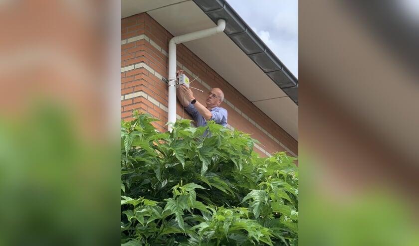 <p>De fijnstofmeter wordt ge&iuml;nstalleerd aan de gevel van een huis.</p>