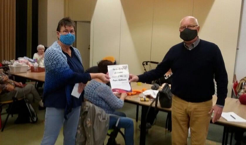 <p>De penningmeester (links) van de handwerkgroep overhandigt de donatie zwart op wit aan Quirien Groenendijk.</p>