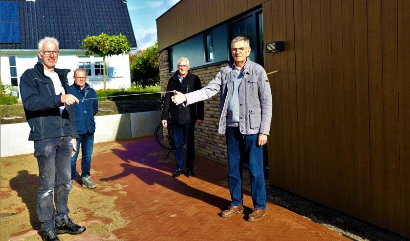 <p>Via een ijzeren staafje krijgt Rinus Bosman de sleutel van het pand van uitvoerder Jan-Willem Palsgraaf. </p>