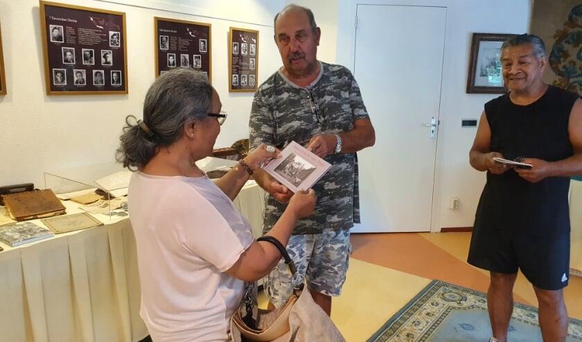 Jaap Waasdorp (m), een van de samenstellers van de expositie, overhandigt een bezoeker het boek 'Moordrecht van Toen'.