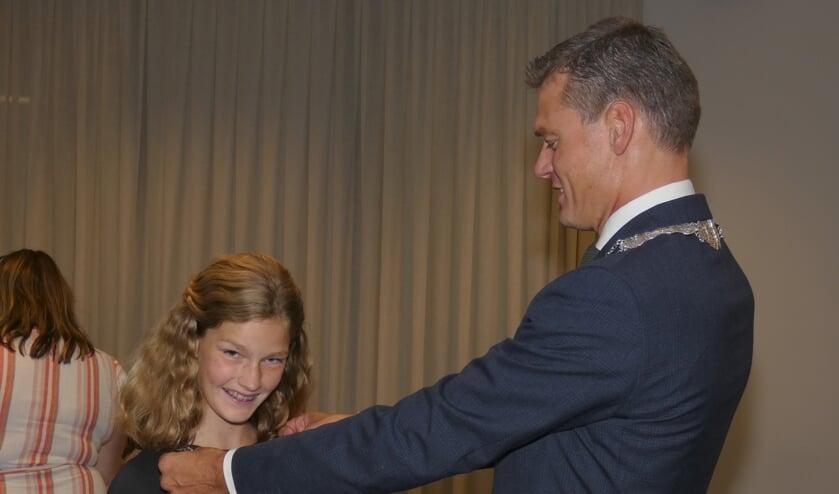 Trots kijkt de eerste kinderburgemeester van Waddinxveen in de camera als zij haar ambtsketen krijgt omgehangen door burgemeester Nieuwenhuis.