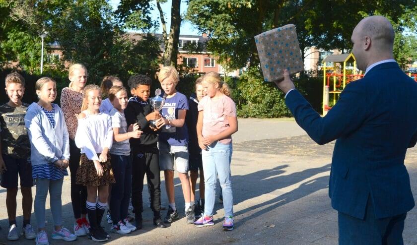 Een beker en een cadeau van wethouder Jan Willem Schuurman voor groep 8 van de Nieuwerkerkse Montessorischool. (foto en tekst: Judith Rikken)