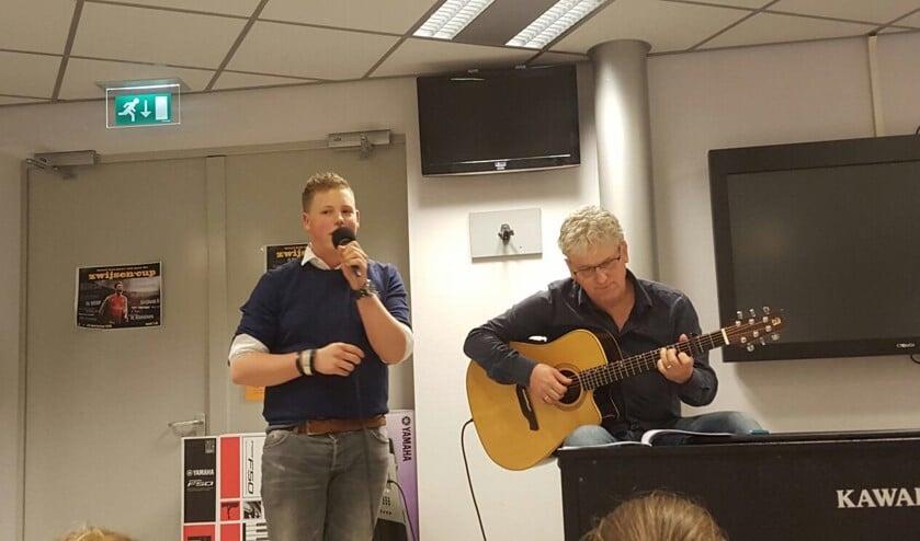 Stan van Hoof zingt tijdens zijn albumpresentatie op het Zwijsen afgelopen dinsdag. Muziekdocent meneer Van Hoof begeleidt hem op gitaar.