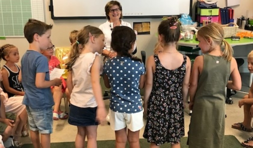 Juf Ella omringd door 'haar' kinderen