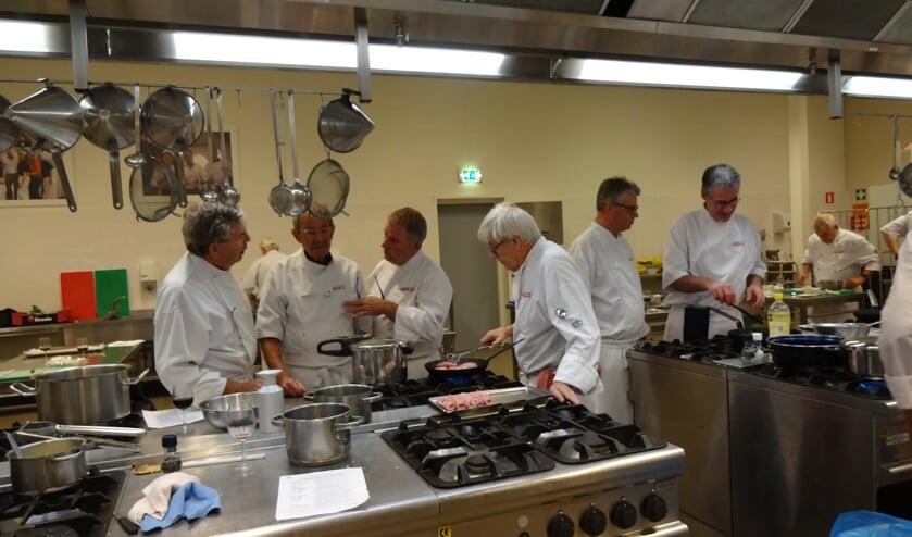 De leden van de gastronomenclub druk bezig met de voorbereidingen. (foto: Ankh van Burk)