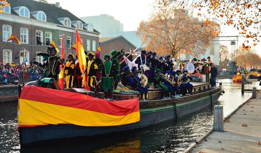 De boot van Sinterklaas wordt begeleid door een kleine vloot van vier schepen, waarop allerlei soorten pieten staan.