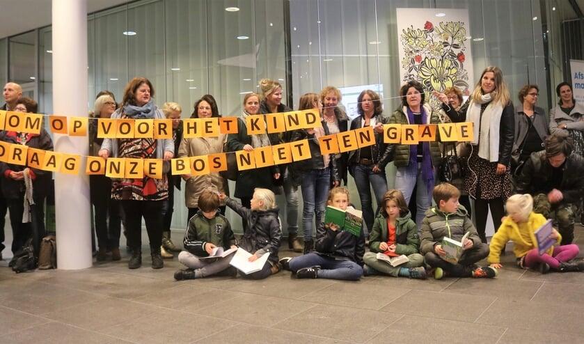 Kinderen, ouders, docenten en medewerkers Biblioplus protesteren op 5 november in de hal van het stadhuis tegen bezuinigingen op de schoolbibliotheek.