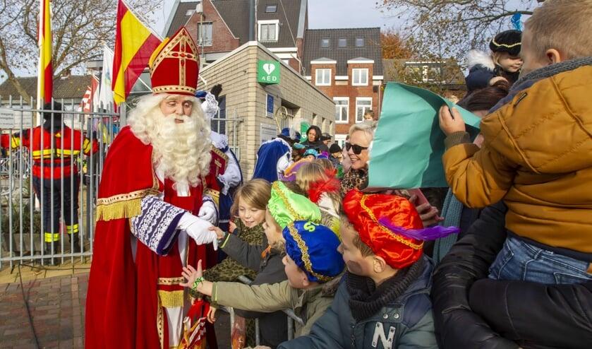 <p>Sinterklaas schudt kinderhanden tijdens de intocht van vorig jaar.</p>