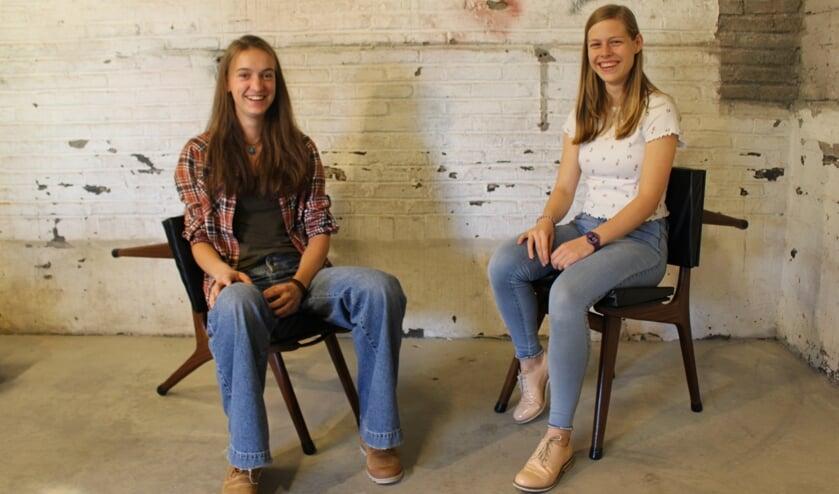 Aila (L) en Yara in hun expositieruimte. Ze zitten op de ontworpen stoelen van Aila.