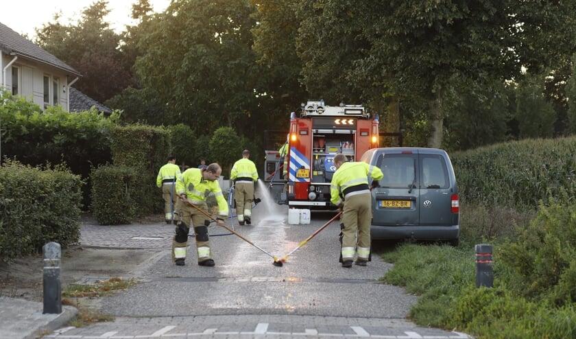 De brandweer reinigt olie op de Kampsestraat in Haps.