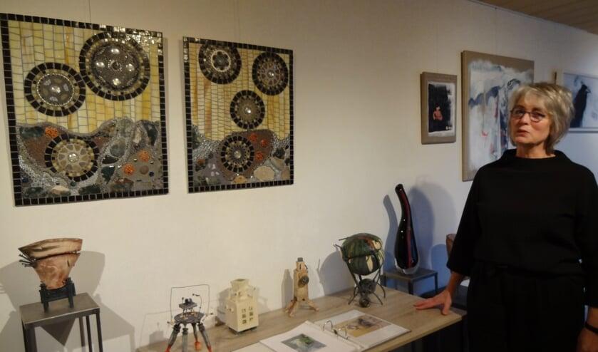 Marion de Goeij bij een gedeelte van haar werk. Aan de wand mozaïeken van Marga Janssen. (foto: Ankh van Burk)