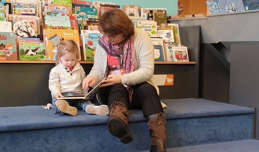 Moeder en dochter genieten van verhalen in bibliotheek Boxmeer.