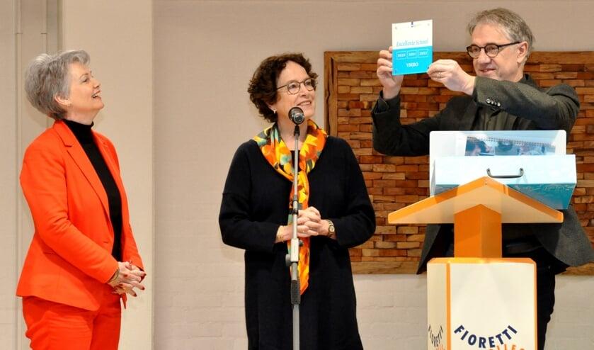 Anita (L) kijkt trots hoe Clemens Geenen van het Fioretti het predicaat in ontvangst neemt.